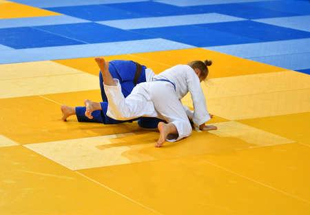 Photo pour Two Girls judoka in kimono compete on the tatami - image libre de droit