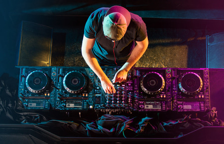 Photo for Handsome DJ playing on CD players during party. - Royalty Free Image