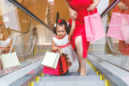 Photo pour mom and daughter on the escalator in the mall with colored bags - image libre de droit