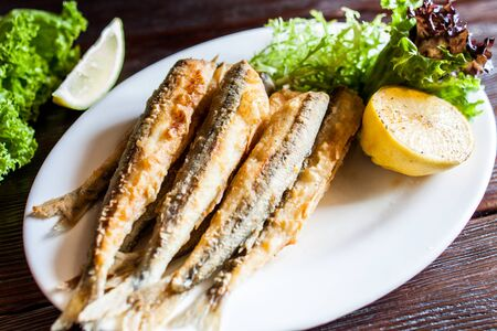 Photo pour Fried small capelin on a plate on a wooden table. A good beer snack. - image libre de droit