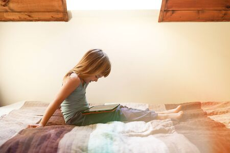 Photo pour toddler girl sitting bed on the looking at tablet on her legs - image libre de droit