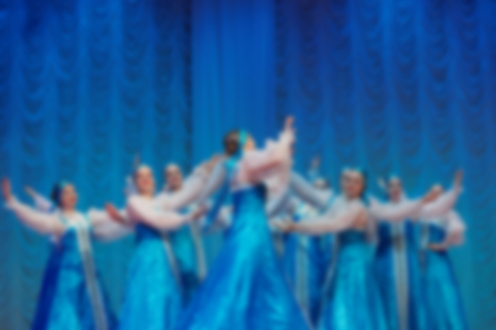 Folk dances of children and teens theme abstract blur background with bokeh effect. Teens in bright blue folk costumes dance Russian folk dance in the concert hall.