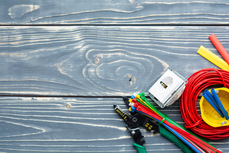 Photo for Different electrician's supplies on gray wooden background. - Royalty Free Image