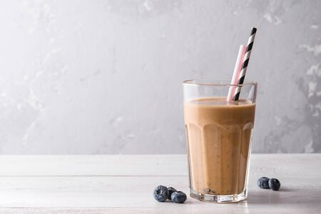 Foto de Chocolate protein shake on a white wooden background. Fresh milkshake with blueberry on a light table. A glass of chocolate smoothie . - Imagen libre de derechos