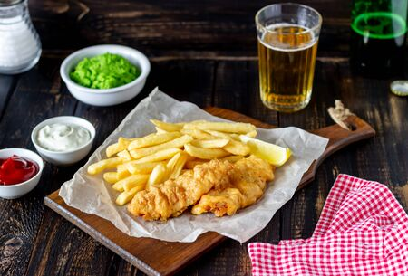 Photo pour Fish and chips on a wooden background. British fast food. Recipes. Snack to beer. Traditional british food. - image libre de droit