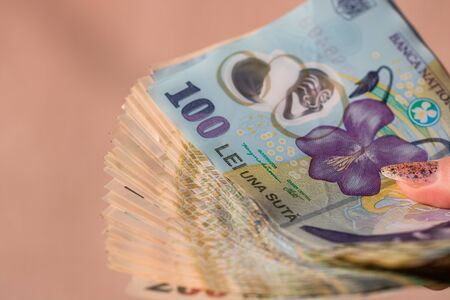 Photo pour Woman hand giving money like bribe or tips isolated . LEI currency banknotes close up. Reward for hard work, finance and business concept - image libre de droit