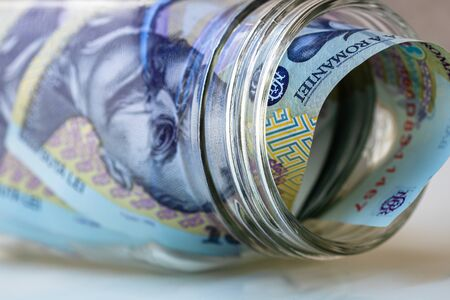 Photo pour Composition with saving money romanian LEI banknotes in a glass jar. Concept of investing and keeping money, close up isolated. - image libre de droit