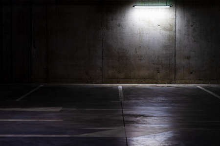 Photo for Empty parking lot with overhead dim light, underground parking garage. - Royalty Free Image