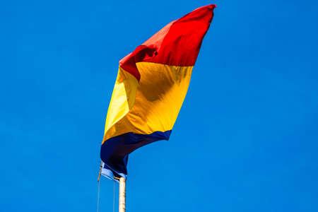 Photo pour Wind blowing romanian flag on a blue clear sky. - image libre de droit