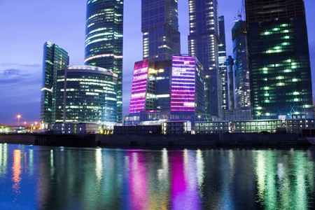 Photo pour glass illuminated skyscrapers at night - image libre de droit