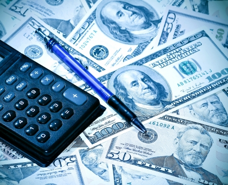 heap of dollars with pen and calculator
