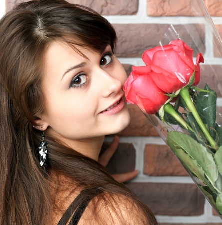 romantic portrait of a pretty teenage girl with a gorgeous bouquet of red roses