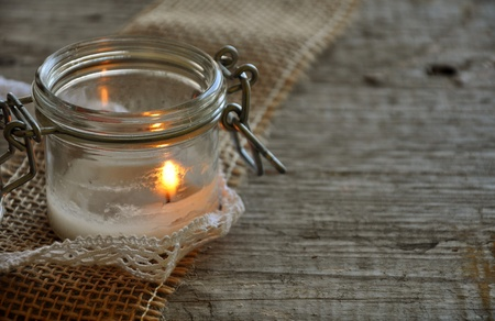 white candle in the jar on jute ribbon and grey wood