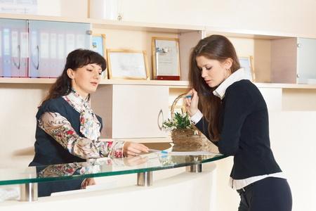 Two woman tolking near help desk in reception office
