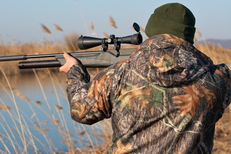 Close up hunter aiming with weapon at the outdoor hunting