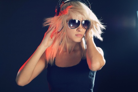 Young girl in dark in expression listening music
