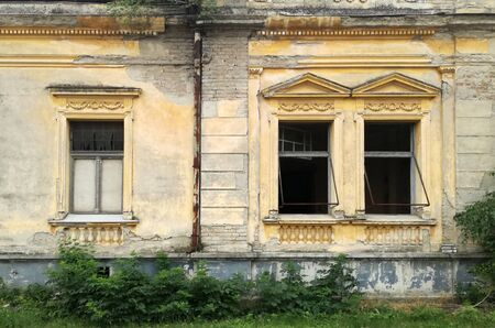 Three windows on the ruined facade of an old abandoned house in Mol, Backa, Serbia