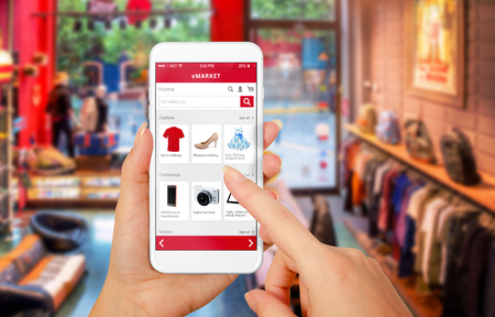 Photo pour Smart phone online shopping in woman hand. Shopping center in background. Buy clothes shoes accessories with e commerce web site - image libre de droit