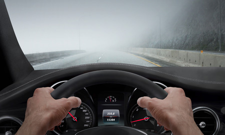 Driving in fog weather. View from the driver angle while hands on the wheel.