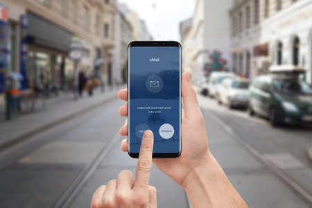 Man use email app on mobile phone. Modern smart phone with round edges and flat user interface design. Street in background.