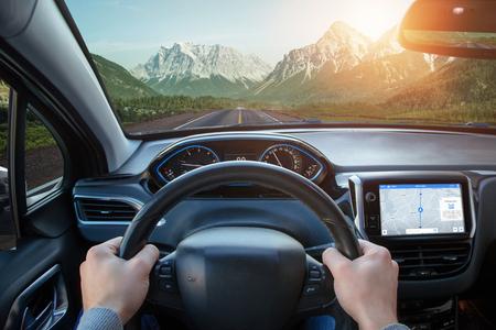Foto de Relaxing car ride through mountainous areas. A view from the driver's angle to car interior and road. - Imagen libre de derechos