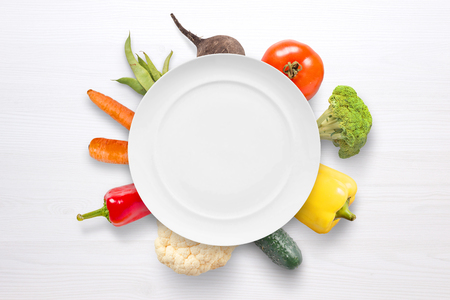 Empty plate with vegetables in background on white wooden surface.