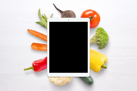 Foto de Blank tablet for mockup. Vegetables in background on white wooden table. - Imagen libre de derechos