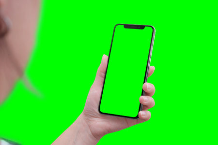Photo pour Modern smart phone with round edges in hand. Close-up. Isoalted screen and background in green, chroma key. - image libre de droit