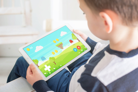 Photo for Boy playing game on white tablet. Home interior in bacgkround. Kid games on mobile devices concept. - Royalty Free Image
