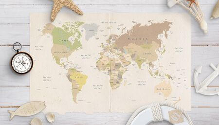 Photo pour World map on a table surrounded by shells, compass, anchor and lifebelt. The concept of holiday planning in distant countries. - image libre de droit