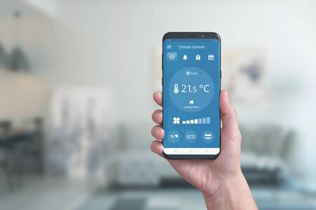 Foto de Smart phone in hand with climate control app. Concept of environmental comfort automation with a simple phone app. - Imagen libre de derechos