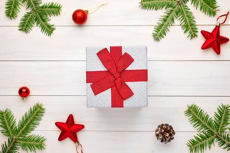Christmas gift on white wooden surface surrounded with fir branches and Christmas decorations.