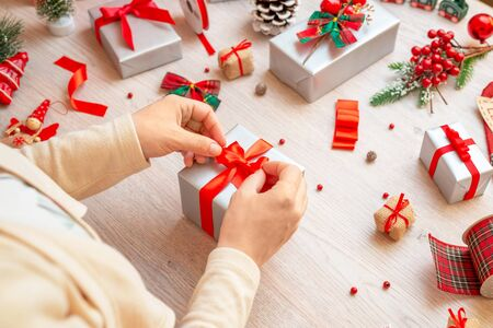 Preparing gifts for Christmas and New Year. The girl prepares a gift by tying a bow. Work table with decorations and decoration material.