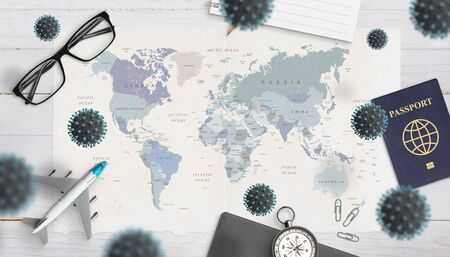 Photo for The concept of danger and inability to travel caused by the coronavirus epidemic. World map, passport, glasses, airplane, compass surrounded by corona viruses - Royalty Free Image
