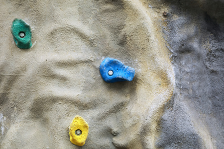 Detail of artificial climbing wall with different sized grips