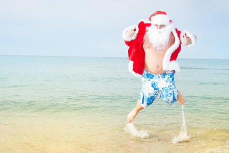 Foto de Funny Santa in shorts on the beach. - Imagen libre de derechos