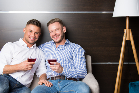 Foto de Love and relationships. Two happy guys together on couch - Imagen libre de derechos