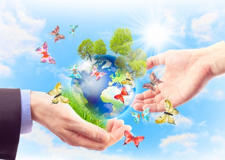 The earth in human hands, grass, trees and butterflies. Concept of heritage earth for future generations