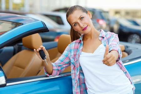 Young happy woman standing near a convertible with the keys in his hand and thumb up - concept of buying a used car or a rental car