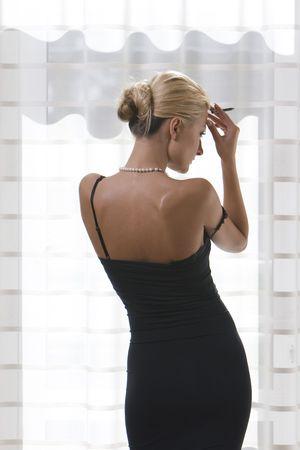 Photo pour Woman with pencil near the window - image libre de droit