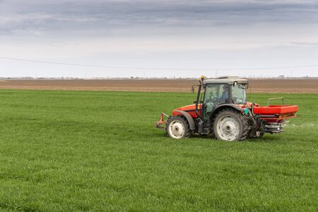 Photo for Tractor spreading artificial fertilizers. Transport, agricultural. - Royalty Free Image