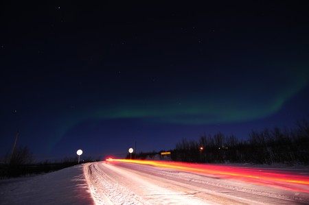 The northern lights over the snow-covered road in north Norway.