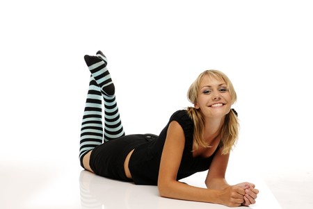 The beautiful smiling young blonde woman with stripy socks on white background