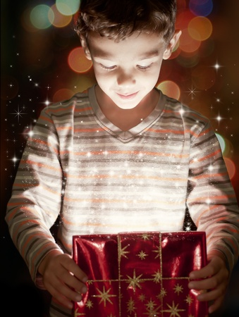 A surprised child opening and looking inside a magic giftの写真素材