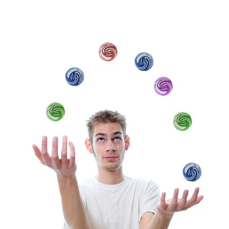 Young man juggling several multicolored balls at once, This concept also applies to multitasking.