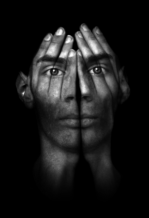 Surreal dark portrait of a young man covering his face and eyes with his hands, but he can see right through them.