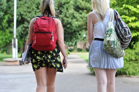 Two young attractive girls wearing skirts walking in front of a public school with their back packs on.