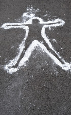 A white chalk outline of a dead body on asphalt cement.