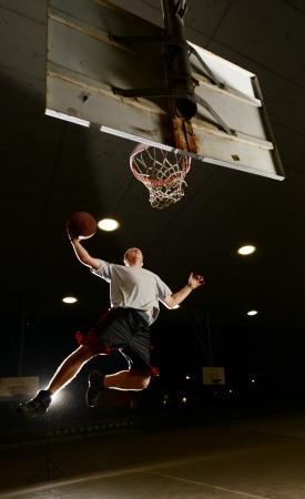 Basket and basektball player jumping with ball and aiming at basket at night