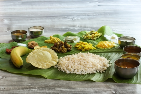 Photo pour Traditional Kerala Onam Sadya   served in Banana Leaf / Vegetarian meal boiled rice curries and Papad served during festivals - image libre de droit